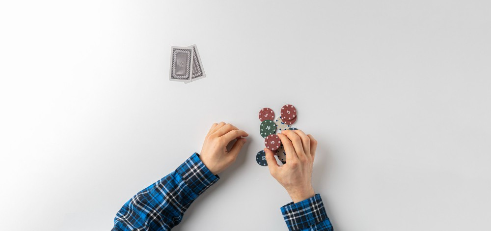 Man holding casino chips and cards.